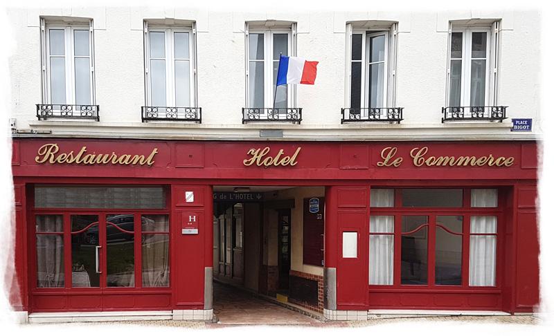 La façade en bois rouge de l'hôtel de Fécamp avec le drapeau français