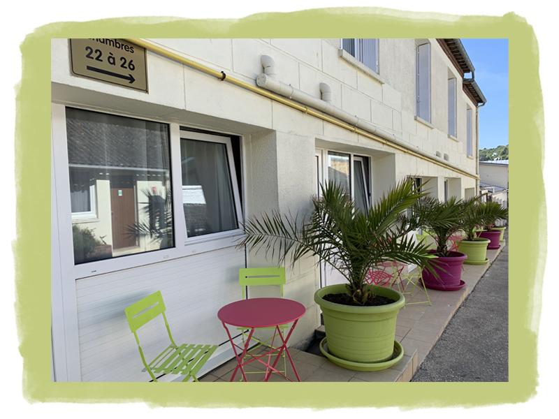 Vue sur la cour de l'hôtel avec ses arbustes et quelques chaises
